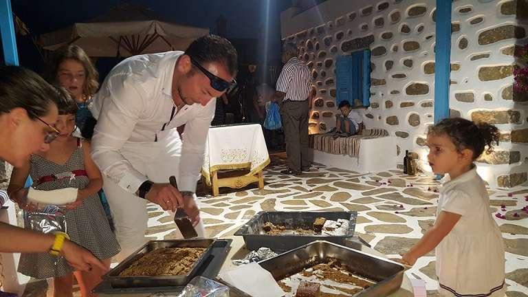 Στην Αμοργό ο Σταμάτης Γιαννακόπουλος -δραστήριος επιχειρηματίας του νησιού και πολύτεκνος πατέρας- μοιράζει τη φανουρόπιτα που μόλις ευλογήθηκε (Φωτογραφία: Ελένη Κουντουρουπή)